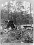 A black and white photograph of three men lounging beneath a makeshift canvas tent on the shore with the river flowing behind them. Their birch-bark canoe sits beside them propped up agains a pine tree