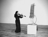 Figure 9. Violinist Mari Kimura, wearing a formal black dress, stands near Guitarbot, a four-stringed robotic instrument on a pedestal that is considerably taller than she is, and looks at it as if it were a fellow musician.