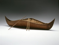A color photograph of a model of a Beothuk canoe with two paddles and a pole.