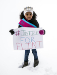 "Amariyanna Copeny, wearing her sash and tiara, holds a protest sign reading ""#Justice For Flint."""