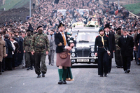 In a large funeral procession, hundreds of people walk behind a hearse, bagpipers, and soldiers dressed in camouflage.
