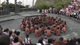 Group of about 30 men wearing checkered sarongs perform in a circle on a circular stage, surrounded by tourists.