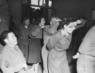 Wacs and nurses form a conga line with combat troops at a rest center in France.