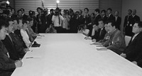 A large table with formally dressed people on the right and left sides. There are a few papers and notebooks in front of them. Photographers and onlookers line the far side of the table.