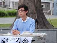 A college student, Wong Ching-Fung, sits at an outdoor table. Photographed from the waist up, his arms rest on the table and his hands are folded. He is looking past the camera into the distance. Paper signs with Chinese text hang from the front of the table