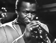Figure 15. Miles Davis, seen in close up, plays the trumpet with his eyes wide open and fixed on a point in infinity to show that he is focused on improvising his solo.
