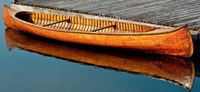 A color photograph of a beautiful cedar strip canoe built by the Lakefield Canoe Company of Peterborough ca. 1925–1930. The canoe uses three wide boards as planking on either side. It is pictured in the water, next to a wooden dock.
