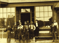 Ella and Bert Morris (far right) and his brother Charlie (far left) pose with their staff in front of the B. N. Morris storefront, ca. 1900.