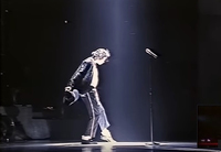 Figure 11. Michael Jackson, leaning forward in a spotlight as he executes dance steps, holds a fedora that he will put on when he steps up to a nearby microphone to begin singing.