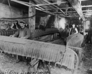 A black-and-white photograph of workers in the canoe factory building canoes.