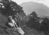 A young couple sits on the mountain slope.