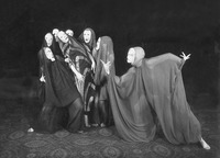 "Photograph of ""Dance of Death II,"" in which the tormenter beast lunges toward Wigman, the tormented martyr, who is supported by six group dancers atop carpet floor and in front of black background. Everyone wears billowing sheer fabric outfits with veils and hard masks. Wigman wears a more narrow dress than the others with dark fabric and lighter color chevron stripes going down the entire garment. She leans back against the group dancers."