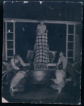 "In this photograph, several characters cluster around Glumov, in clown white, who is holding a character in checked trousers (Mamaev) upside down by his feet. A sign in front of him reads ""ARA"" (American Relief Administration), while behind him is a structure with two ladders and a bar: an inner proscenium."