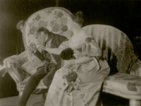 Khlestakov (Garin) and Anna Andreevna (Raikh) sit on an oversized sofa. In this photograph, he holds her pinkie on a teaspoon to kiss it.