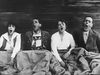Two men and two women sit under a blanket, yawning.