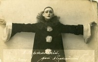 Photograph of Vertinsky in the costume of Black Pierrot in a black smock with white pompoms and cuffs. His black skullcap, eyebrows, and lips contrast sharply with his white-painted face.