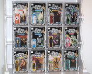 "A photograph showing a set of 12 action figures, still in their plastic packaging, from the Star Wars franchise. Each action figure is included on the bottom left-hand side of the packaging with a large photograph of the actor or character taking up the majority of the package. Each package also includes the words ""Star Wars"" written in silver letters at the top center of the package accompanied by the gold starwars logo and the characters' name in a colored box beneath. Each package is also branded with the manufacturer name: ""Kenner."" The top row includes 4 action figures: Luke Skywalker wearing a white tunic, brown pants, and a black belt (with a black and orange color scheme), Princess Leia Organa wearing a white dress (with a black and blue color scheme), Ben (Obi-Wan) Kenobi wearing a brown robe (with a black and yellow color scheme), and Han Solo wearing a white shirt, black pants, and a black vest (with a black and green color scheme) from left to right. The middle row also includes 4 action figures: See-Threepio (C-3PO), a gold-encased robot (with a black and blue color scheme), Artoo-Detoo (R2-D2), a white, silver, and blue robot (with a black and blue color scheme), Darth Vader wearing a black cloak and black helmet (with a black and yellow color scheme), and a Stormtrooper in a white, plastic full body suit with a helmet (with a black and red color scheme) from left to right. The bottom row also includes 4 action figures: Chewbacca, a brown, hairy creature with a machine gun slung over his shoulder (with a black and yellow color scheme), Jawa, a small creature with a brown cloak (with a black and yellow color scheme), one of the Sand People wearing brown robes and a green-ish face mask (with a black and green color scheme), and a Death Squad Commander wearing a gray suit, black gloves, and a black helmet (with a black and blue color scheme)."