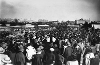 An black and white photo of a crowd gathered in a plaza. The photo is taken over the hat-covered heads of the people, showing the crowd stretching into the distance and towards the city further away.