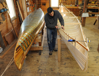 Dylan Schoelzel makes wood-and-canvas canoes at Salmon Falls Canoe in Massachusetts. Note the metal bands on the canoe form at left.