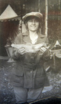 A black-and-white photograph of Mae Marshall holding a fish, a campsite is in the background.