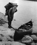 Arthur Carhart, at the Superior National Forest in 1920, demonstrates how to stack and carry two canoe packs.