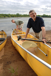 A color portrait of Mike Cichanowski next to a group of Kevlar canoes on the shore.