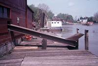 A color photograph of the exterior of Kishman Fish Co. building ramp over dock towards water.