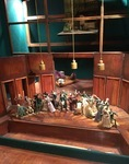 "Set model (reconstruction) in mahogany and green baize with the mannequins from the dumb show positioned in a semi-circle, center, on tiny platforms. Upstage at floor level is one of the mobile stages, preset with the furniture from episode 7, ""Behind a Bottle of Tolstobriushka."" High in the flies is the set for episode 4, ""After Penza,"" with its distinctive curved staircase."