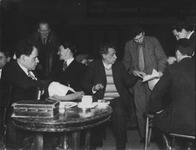 This rare photograph of Eisenstein and Meyerhold together in rehearsal depicts a bustling creative atmosphere with Meyerhold, center, pointing out something on a piece of paper and Eisenstein, left, sitting behind a round table. Those in the photograph—all men—are in jackets and ties, except Meyerhold, who wears a striped sweater under his open blazer.