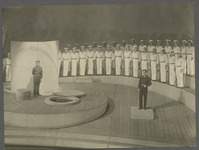 Two characters talk downstage at a distance from one another on a set constructed around simple circles and curves. Upstage of them sailors stand in rows that emphasize the sweeping spiral of the stage.