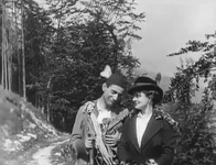 A young man and woman hike along a forest trail.