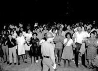 African Americans sing protest songs and clap their hands on the lawn of the Executive Mansion in Raleigh, NC, 1963.