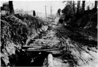 Dirt road repaired with pine poles in the pre-automobile era
