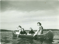 A black and white photograph of four women in a canoe on a lake. They are all looking at the camera and smiling as two of the women push their oars through the lake water, and the other two sit in the middle of the canoe.