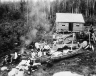 A group of scattered forest rangers, sitting, socializing, and relaxing on the grass alongside canoes. A cabin is in the background.