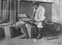 Edwin Tappan Adney, the expert on bark canoes, studies one of his models in 1896.