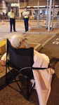 Photographed from the back, Wong Fung-Yiu (Old Lady Wong) sits in a folding chair in the street. She has white hair, wears glasses and an air pollution mask, and is covered with a blanket. Two security officers stand across the street, facing her