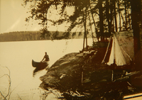 A black and white photograph of a campsite of a man, Jules Fox Marshall, canoeing up to a campsite with a canvas tent supported by birch tree limbs.