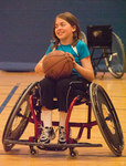 Shanti, age eleven, in a sports wheelchair playing basketball.