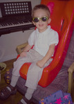 Jaymason, a white boy in sunglasses, sits in a Tumble Forms chair.