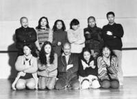 This is a black and white cast shot showing eleven people, approximately in their thirties, arranged in a studio facing the camera in two rows. Five people kneel in the front row and six stand behind them. All eleven have their arms crossed or hands crossed in front of their torsos, and each makes a different strange facial expression, such as smirking, grinning, looks of exaggerated shock or suspicion, or unsettling stares. One woman sticks out her tongue. Three of the men have shaved heads, and all of the women have long, often curly or wavy black hair. They are bundled in layers of everyday winter clothing, including sweaters, coats, and scarves. The man in the front center appears to be wearing a bathrobe.
