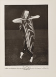 A sepia photograph of Mary Wigman from Death Dance II, here portrayed solo. She wears the chevron-striped draped costume and mask, bending her arms outward and meeting her fingers together below her chin. She stands in a position with one leg behind her and toes pointed atop a carpet floor.