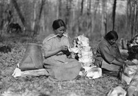 A black-and-white photograph of two women making birch-bark containers on the ground outside.