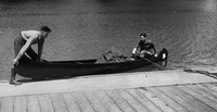 A black-and-white photo of Sevareid and Port getting into a canoe from a wooden pier.