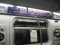 "A photo of an advertisement on a New York City subway train that says in capital purple letters ""The man by the door will someday be your boss."" Beneath those words is the website ""u-r-connected.com."""
