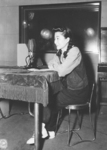 Iva Toguri photographed before the microphone at Radio Tokyo in September 1945.