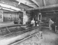 A black-and-white photograph of workers in the Canadian Canoe Company factory applying varnish to canoes.