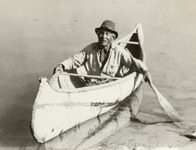 A black-and-white photograph of a figure kneeling in and paddling a canoe.