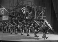 A row of actors, identically clad in prozodezhda (utilitarian uniform costumes), bowing in unison, traverse the forestage in front of Liubov Popova's constructivist playground of a set.