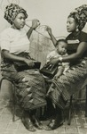 Two women wearing cotton print wrappers with mat pattern.